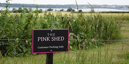 The Pink Shed beauty salon sign overlooking the River Orwell in Suffolk